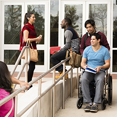 A group of college students outside a lecture hall building