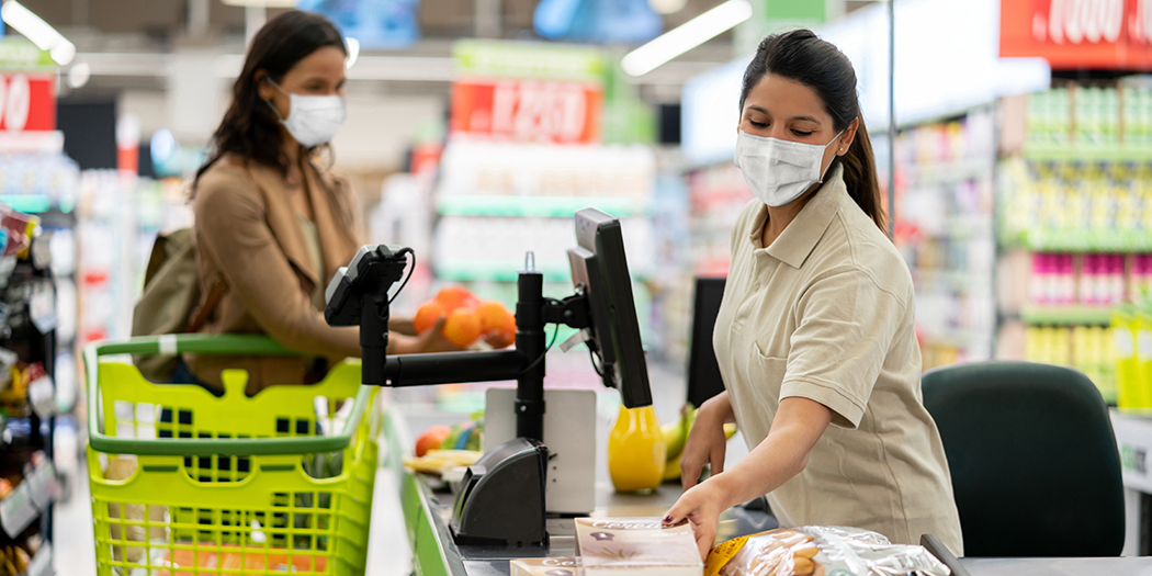 A cashier in a mask scans a woman's groceries