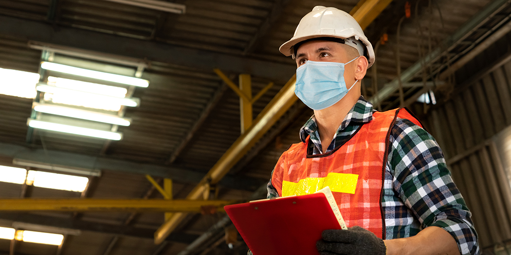 A man in a surgical mask and safety vest surveys the manufacturing floor