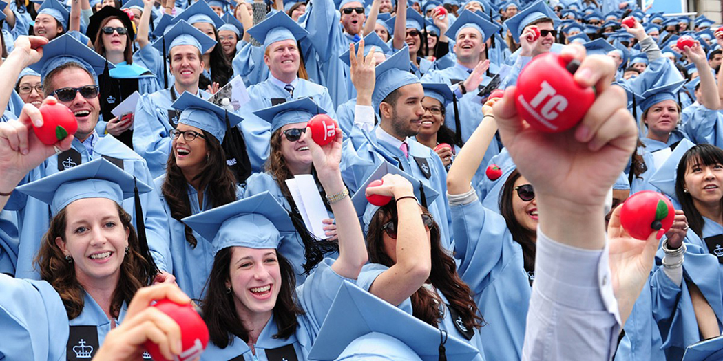 Teachers College graduates in their graduation caps and gowns hold foam apples that read